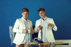 Twin brothers with happy faces. Businessmen wearing shirts, jackets and underpants. Ironing board with iron and clothes rack on blue background. Fashion stock image
