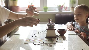 Twin brothers helping her mother to grind coffee. In the kitchen in the morning stock footage