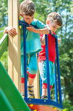 Twin brothers looking down from the playground Royalty Free Stock Images