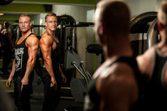 Twin brothers looking in mirror after body building workout in f Royalty Free Stock Images