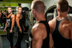 Twin brothers looking in mirror after body building workout in f Stock Photos
