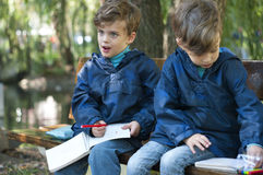 Twin brothers in the park. Four year old identical twin boys seat on the bench in the park. They are dressed in anoraks. They draw with pens in notebooks Royalty Free Stock Photo