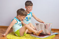 Twin brothers play with book Stock Images