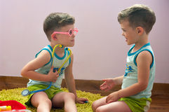 Twin brothers play in doctor Stock Photo