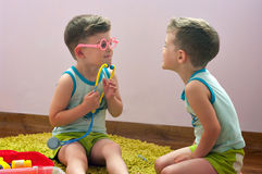 Twin brothers play in doctor Royalty Free Stock Image
