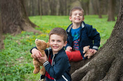 Twin brothers play in the forest. Four year old identical twin brothers sit on the tree. They are holding a toy puppies. Season - spring Stock Image