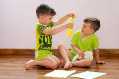 Twin brothers play with paper Royalty Free Stock Image