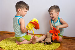 Twin brothers play with puppets. Three year old identical twin boys sit on the carpet and play with puppets royalty free stock image