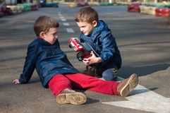 Twin brothers play with a toy car. Four year old twin boys sit on the road and play with the toy car. Season - spring Stock Image