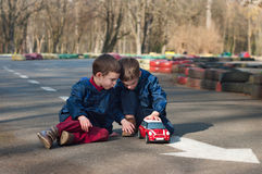Twin brothers play with a toy car. Four year old identical twin boys sit on the road and play with the toy car. Season - spring Royalty Free Stock Photos