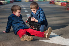 Twin brothers play with a toy car. Four year old identical twin boys sit on the road and play with the toy car. Season - spring Stock Photography
