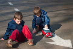 Twin brothers play with a toy car. Four year old identical twin boys sit on the road and play with the toy car. Season - spring Stock Images