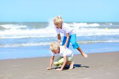 Twin brothers playing on the beach Stock Image