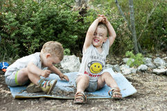 Twin brothers playing in the dust. Identical twins sit on the mat outdoors. They play with the soil. The boys are very soiled with dust. One of the brothers Royalty Free Stock Photography