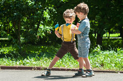 Twin brothers playing with lollipops in hand Stock Photography