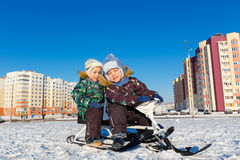 Twin brothers posing on snow scooter Stock Photo