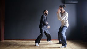 Twin brothers practicing tai chi blows in the training hall.  stock video