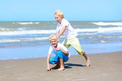Twin brothers running and jumping on the beach Royalty Free Stock Photos