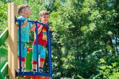 Twin brothers stend on the balcony of the playground Stock Photography