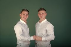 Twin brothers support each other. Happy men fist bumping. Twins wearing blue shirts and pants. Family, brotherhood and friendship concept. Models standing Royalty Free Stock Photography