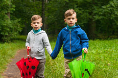 Twin brothers with umbrellas Stock Photos
