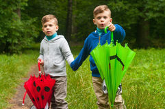 Twin brothers with umbrellas Stock Image