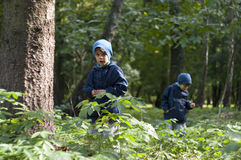Twin brothers in the woods. Four year old identical twin boys in the forest. They are dressed in anoraks and hats Stock Photo