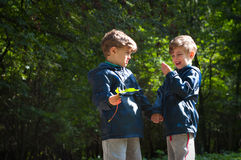 Twin brothers in the woods. Four year old identical twin boys in the forest. They're looking at the leaf in hands. They are dressed in windbreakers and Royalty Free Stock Images