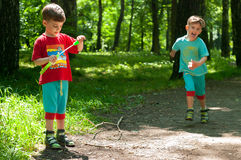 Twin brothers in the woods. Three year old identical twin boys frolic on the forest footpath. One of them blows soap bubbles. Summertime. Children wearing Royalty Free Stock Photos