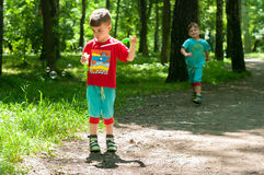 Twin brothers in the woods. Three year old identical twin boys frolic on the forest footpath. One of them blows soap bubbles. Summertime. Children wearing Stock Photo