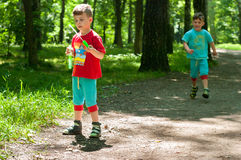 Twin brothers in the woods. Three year old identical twin boys frolic on the forest footpath. One of them blows soap bubbles. Summertime. Children wearing Royalty Free Stock Photography