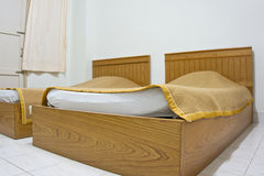 Twin brown bed near window at hotel Royalty Free Stock Photos
