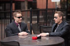 Twin businessmen at outdoor cafe Royalty Free Stock Photos