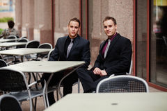 Twin businessmen at outdoor cafe Stock Photo