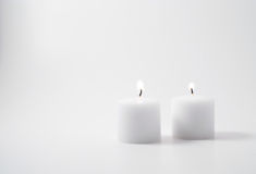 Twin candles. Two flames on twin candles on a neutral background Royalty Free Stock Photography
