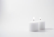 Twin candles. Two flames on twin candles on a neutral background Stock Photos