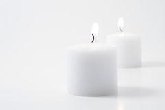 Twin candles. Two flames on twin candles on a neutral background Royalty Free Stock Photo
