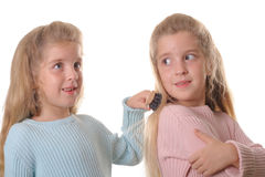 Twin child brushing sisters hair. Shot of twin child brushing sisters hair Stock Image