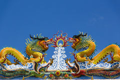 The twin Chinese dragon on temple roof. In Thailand Stock Photos