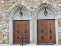 Twin church doors. Wood, heavy iron . Arches. Lanterns above. Mirror image church doors Stock Photo