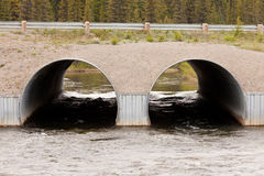 Twin culvert tunnel road bridge crossing wild river Stock Photography