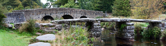 Twin Dartmoor Bridges. Twin Bridges over the East Dart river on Dartmoor at Postbridge showing the ancient clapper bridge in front of the road bridge Royalty Free Stock Photography