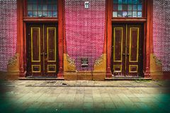 Twin doors and red bricks wall of the historic `Toko Merah` or Red Store est. 1730, Old City Tourism Area. royalty free stock image