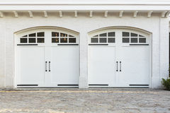 Twin double garage doors to a white home Stock Image