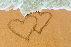 Twin double heart drawn on sandy beach with wave approaching Stock Photography