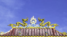 Twin dragon statue on roof. Twin dragon statue on chinnese roof with blue sky background Royalty Free Stock Photo