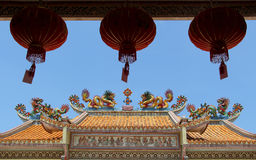 Twin dragons on the roof of Chinese temple. Twin dragons statue on the roof of Chinese temple with chinese lantern and blue sky Royalty Free Stock Photo