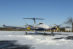 Twin engine aircraft with turboprop power plant under snow in sunny winter day Royalty Free Stock Photos