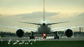 Twin engine commercial airplane starting takeoff from the airport in the evening, rear view Royalty Free Stock Photography