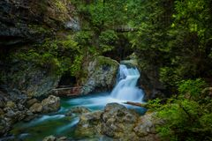 Twin Falls in Lynn Canyon Park, North Vancouver, Canada. Twin Falls in Lynn Canyon Park with footbridge, North Vancouver, Canada. Long exposure royalty free stock images